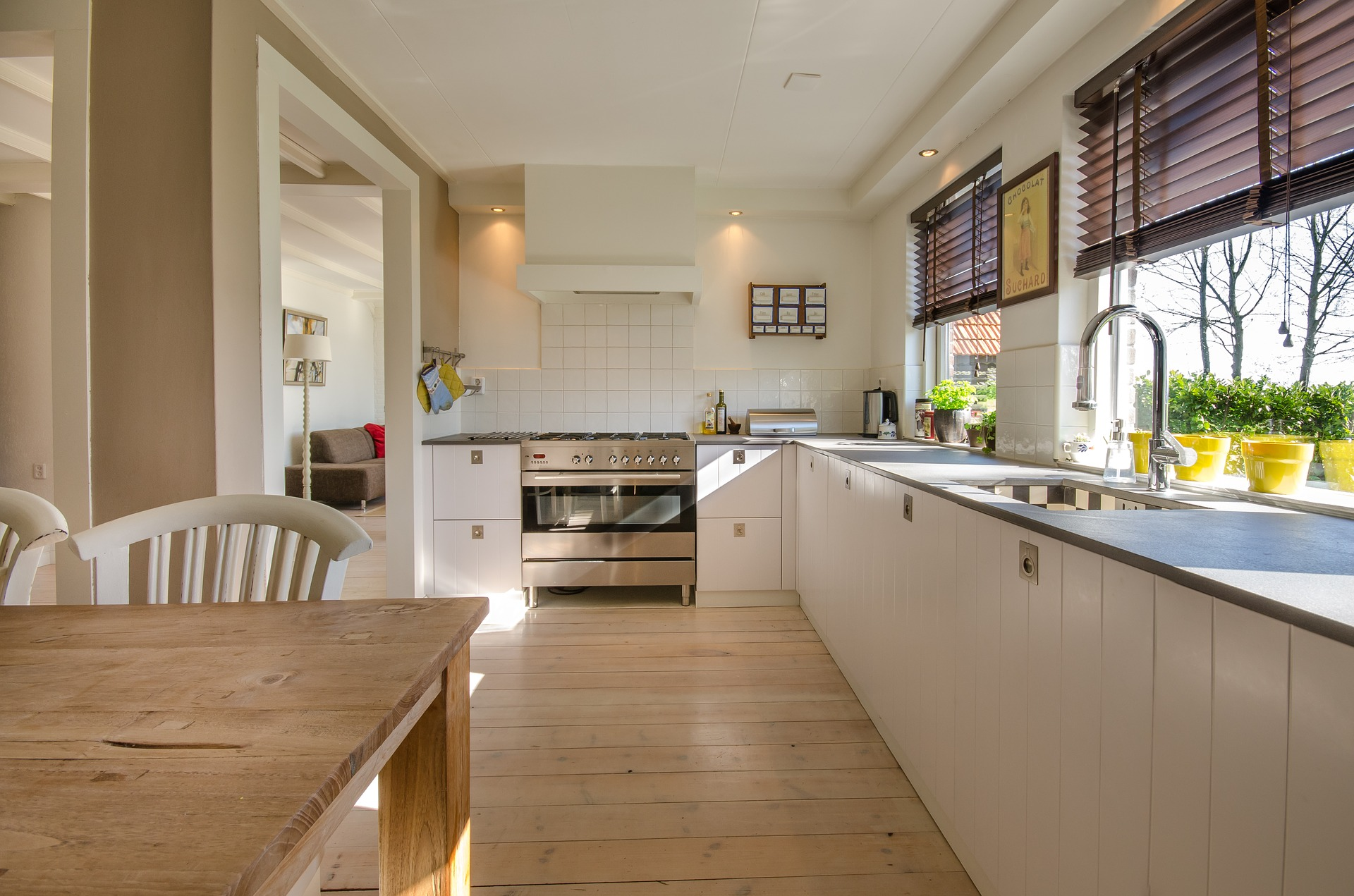 A large, ppen kitchen with white appliances and hardwood floors