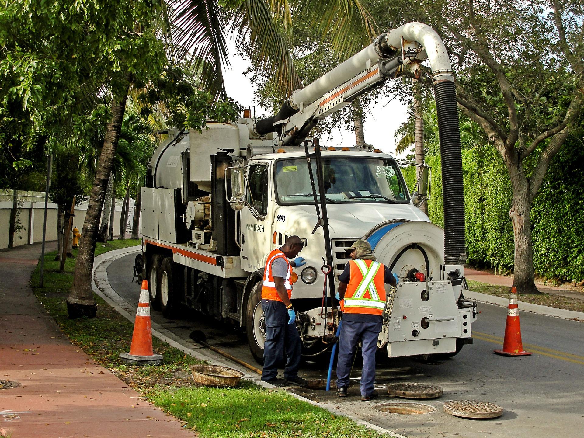 Men in orange vest standing in front of truck working on sewer