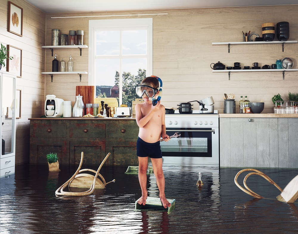 A male child about 10 years old in swim trunks and a snorkeling mask, standing on a box in the middle of a flooded kitchen, where Erica's Plumbing Services in South Florida could help the homeowners.