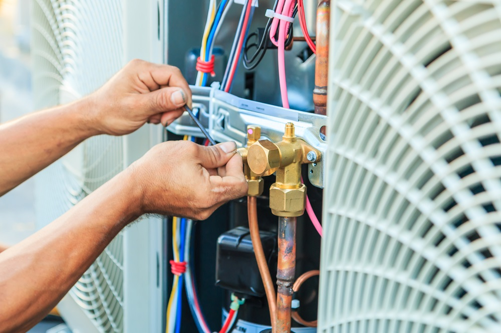 Two hands assembling parts on air conditioner, posing the question, How does air conditioning work in Boca Raton?