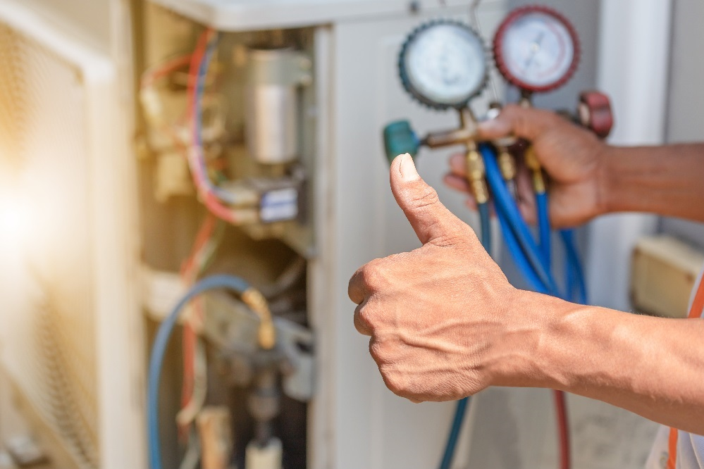 A man's right hand holding a red and blue pressure gauge in his right hand, while his left hand is giving a thumbs up in front of an AC unit, posing the question, How much does it cost to install air conditioning in Boca Raton, Florida