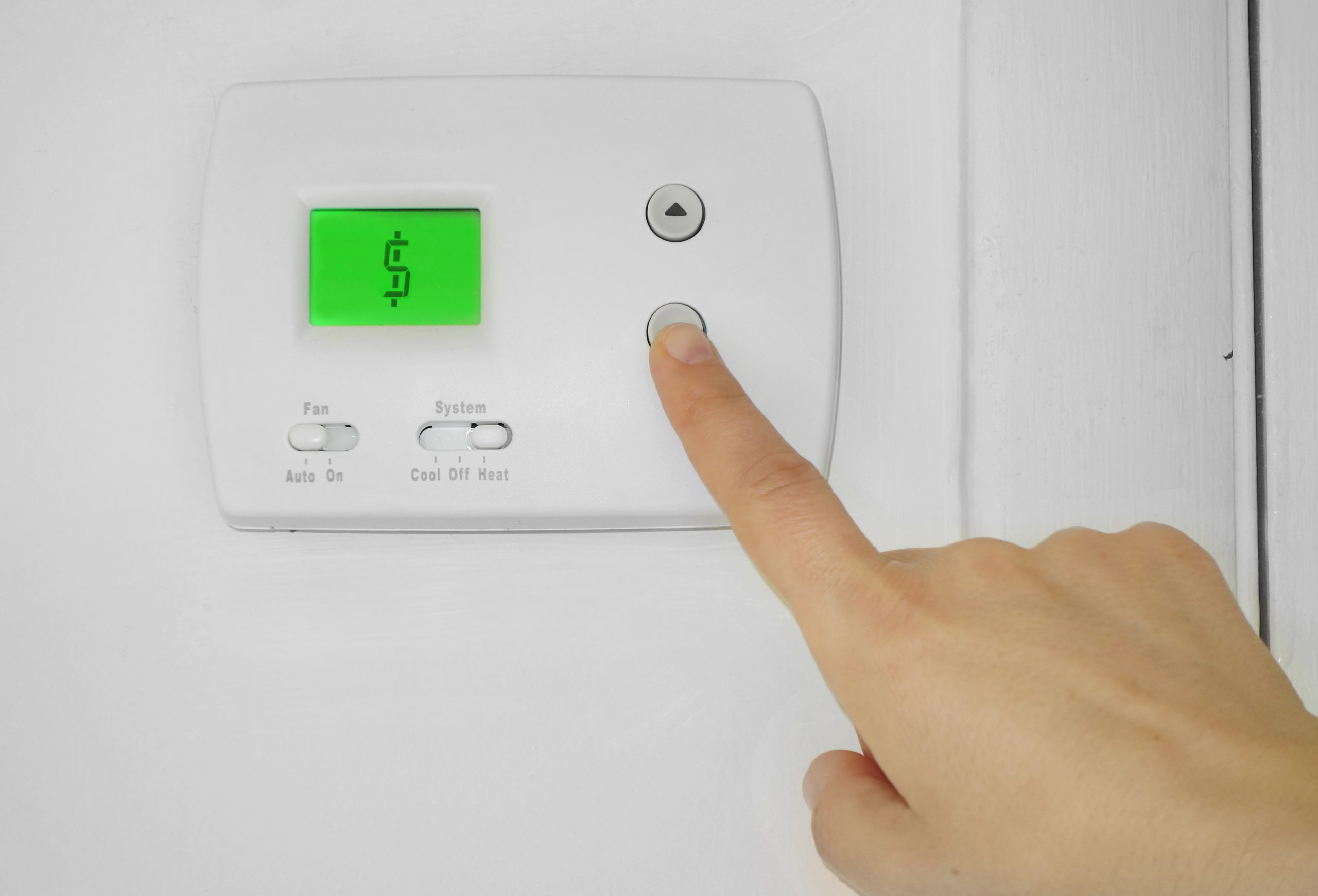 A finger pressing a button on an air conditioner unit, whose screen is green and displaying a $ dollar sign, posing the question, How much is an air conditioning unit in Boca Raton?