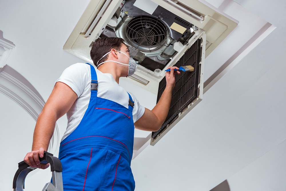 A repair man wearing a white shirt and bright blue overalls standing on a ladder cleaning an air conditioner installed in the ceiling, posing the question, How often should air conditioning be serviced in Florida?