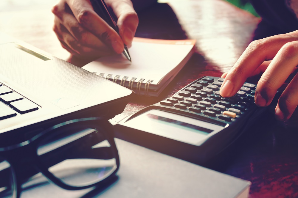 Closeup of a desk with reading glasses, corner of a laptop, and two hands writing on a small pad of paper and pushing a button on a calculator, posing the question, How much to install air conditioning in Coral Springs, FL?