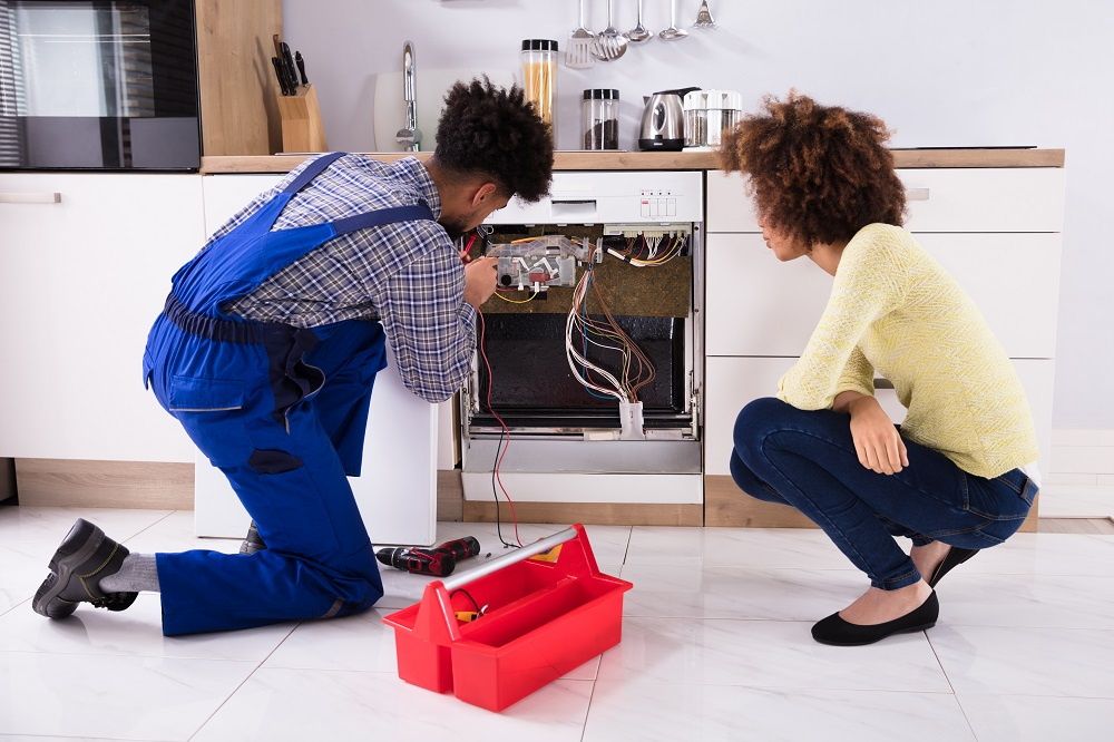 A man in blue overalls showing a woman how to plumb a dishwasher in her Boca Raton, FL.